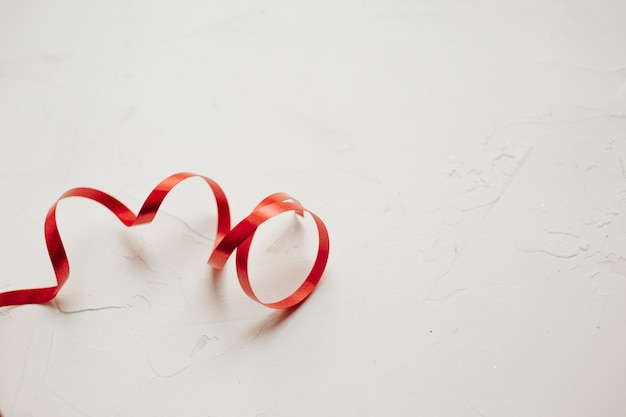 Festive red ribbon on white plastered background, beautiful texture, copy space
