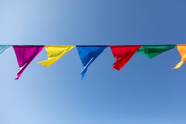 푸른 하늘 배경에 여러 가지 빛깔의 삼각형으로 만든 축제 리본. 축하 파티.
