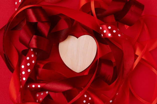 Festive ribbon and wooden heart on the red