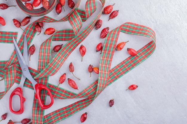Nastri festivi, forbici e fianchi su sfondo bianco.