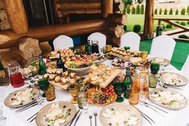 Праздничный богатый круглый стол с белой скатертью и стульями, подается с разнообразными вкусными блюдами, оригинальными закусками и напитками. шведский стол на природе