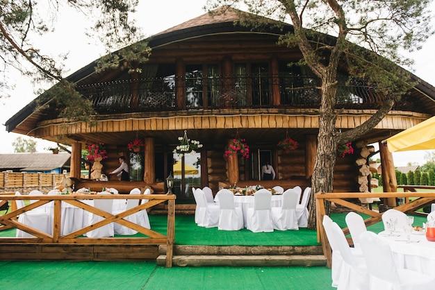 Праздничный богатый круглый стол с белой скатертью и стульями, подается с различными блюдами и напитками