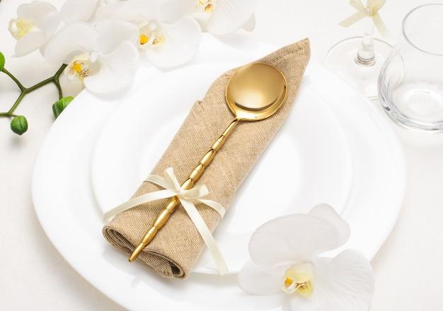 Праздничная романтическая сервировка стола с бежевой салфеткой и белыми орхидеями на белой скатерти