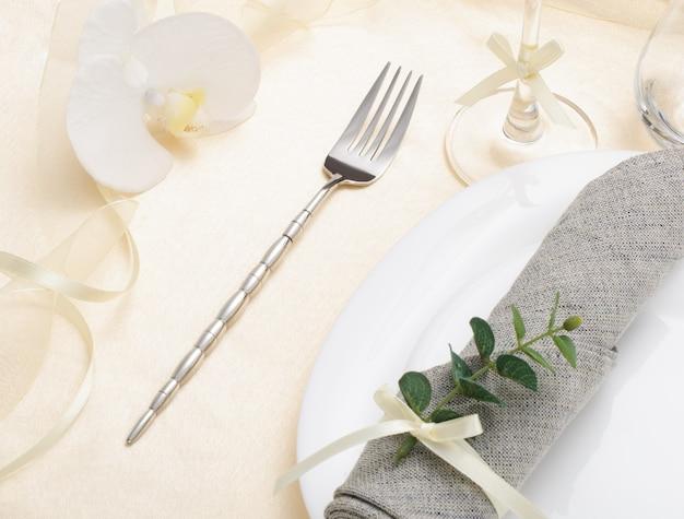 Праздничная романтическая сервировка стола столовым серебром, серой салфеткой и белой посудой на бежевой шелковой скатерти