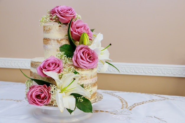Festive rustic cake with flowers, rose and lily.