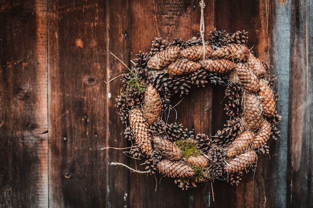 Праздничный деревенский рождественский венок из сосновых шишек на темно коричневой деревянной стене.