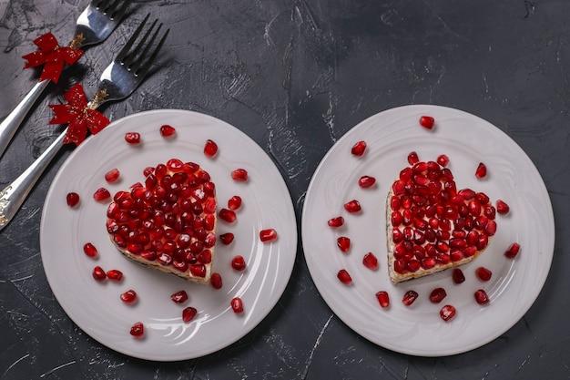 Праздничный салат слоями в форме сердца, украшенный зернами граната на темном фоне, горизонтальная ориентация, крупным планом, вид сверху