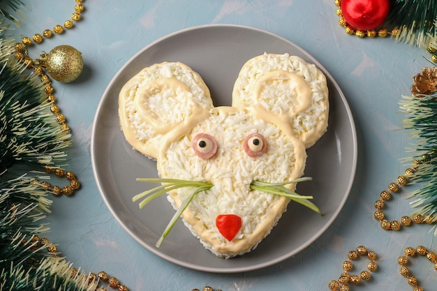 Festive salad mouse for 2020 on light blue background, symbolic food for new year, top view, horizontal orientation