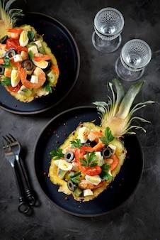 エビ、キウイ、オリーブ、ソフトチーズ、ウズラの卵、パイナップルプレートのチェリートマトのお祝いサラダ。