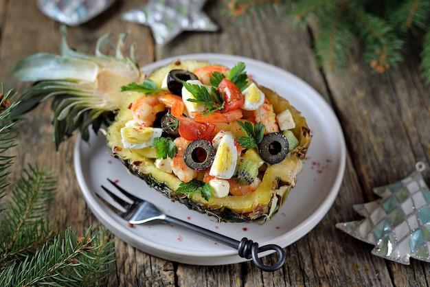 Festive salad of shrimp, kiwi, olives, soft cheese, quail eggs, cherry tomato in pineapple plates.