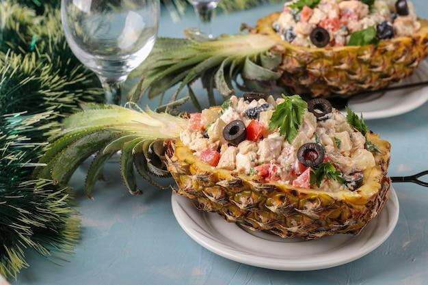 水色の背景、新年、バレンタインデー、ロマンチックなディナー、クローズアップ、水平方向のパイナップルの半分に鶏肉のお祝いサラダ