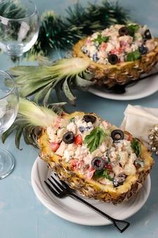 水色の背景にパイナップルの半分に鶏肉のお祝いサラダ、