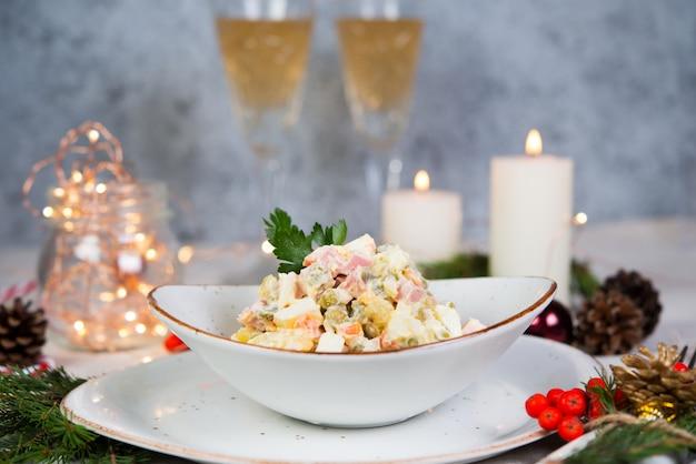 소시지, 야채와 마요네즈 축제 샐러드. 샐러드, 크리스마스 장식 및 garlands 크리스마스 테이블 설정.