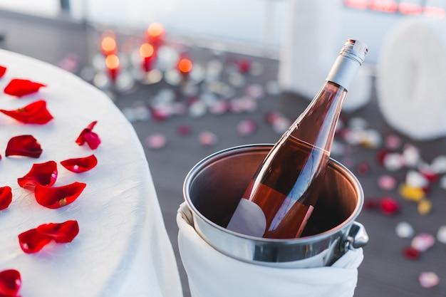 Праздничный сервированный стол для романтического ужина с бутылкой вина