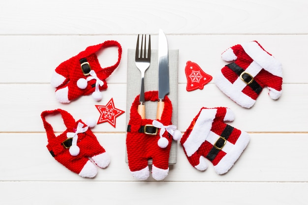 Festive set of fork and knife. top view of new year decorations and santa clothes and hat. close up of christmas concept
