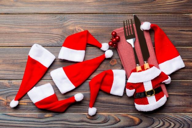 나무 배경에 포크와 나이프의 축제 세트. 새해 장식과 산타 옷과 모자의 최고 전망. 크리스마스 개념의 닫습니다.