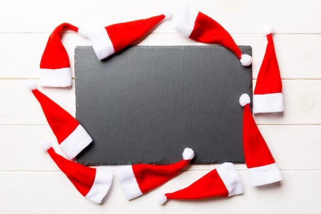 나무 배경에 산타 클로스 모자로 장식 된 접시의 축제 세트. 상위 뷰 크리스마스 저녁 식사 개념입니다.