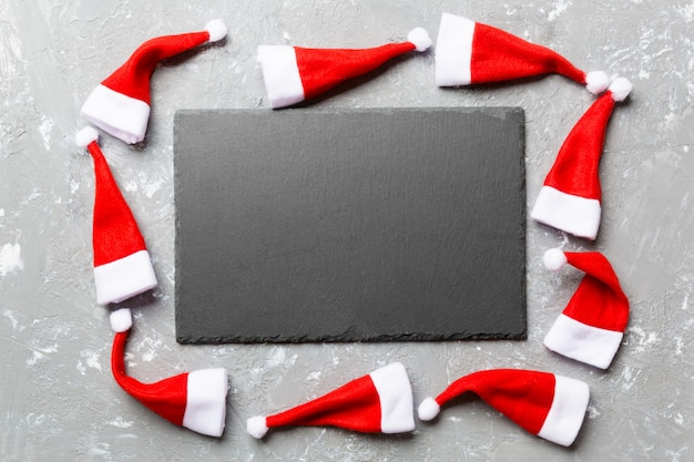 Festive set of plate decorated with santa claus hat on cement surface