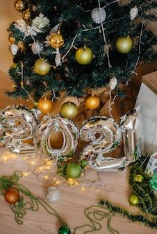 クリスマスツリーの背景に番号2021のお祝いの銀の金属ボール