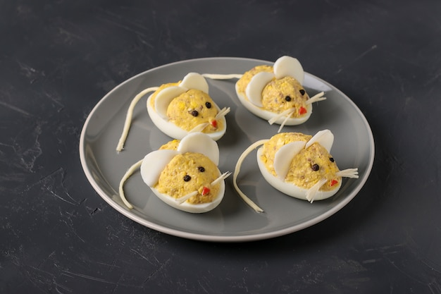 Праздничная закуска мыши из фаршированных яиц с печенью трески на темном фоне, кулинарная идея для детей