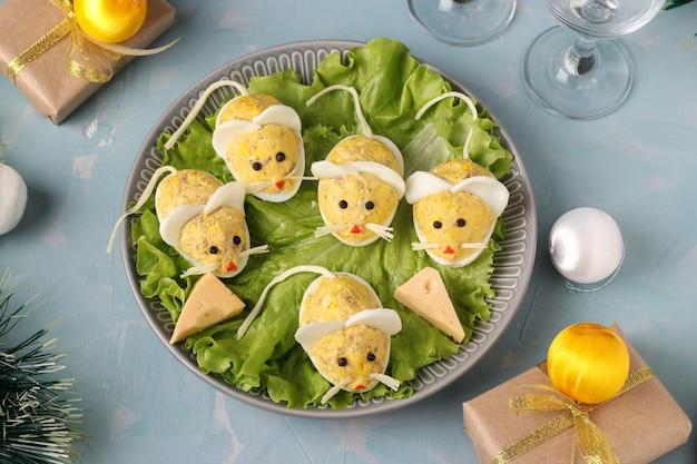 お祝いスナック水色の背景にタラ肝油を詰めた卵で作られたマウス、上面図、クローズアップ