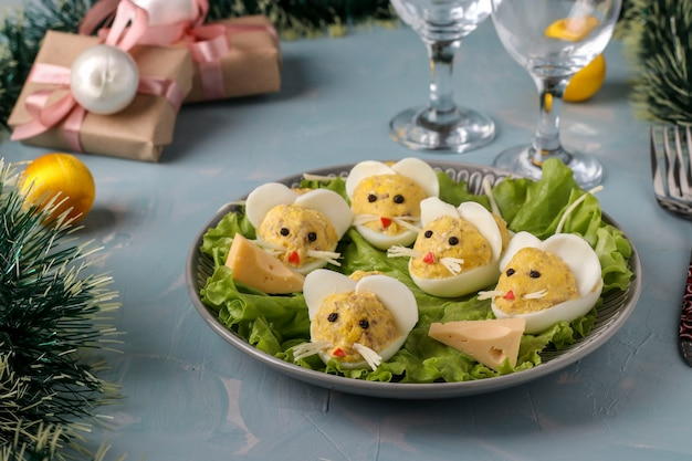 Festive snack mice made of stuffed eggs with cod liver on a light blue background