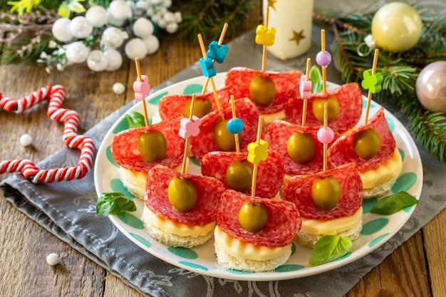 クリスマステーブルのカナッペのお祝いスナックパンチーズサラミとオリーブのカナッペ