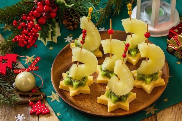 クリスマステーブルのカナッペのお祝いスナックチーズキウイとパイナップルのフルーツカナッペ