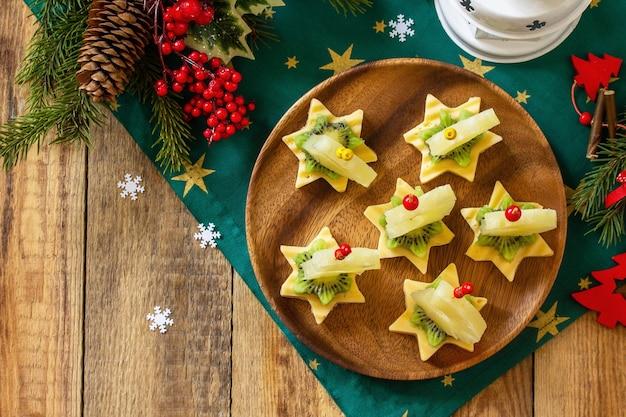 クリスマステーブルのカナッペのおやつチーズキウイのフルーツカナッペコピースペース