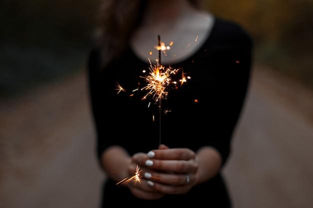 Праздничный бенгальский огонь. женские руки держат яркий бенгальский огонь.