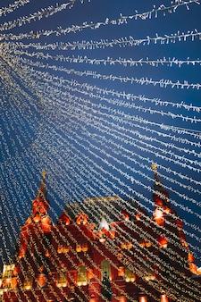 Праздничные сверкающие гирлянды и золотые украшения на улице с новым годом и рождеством.