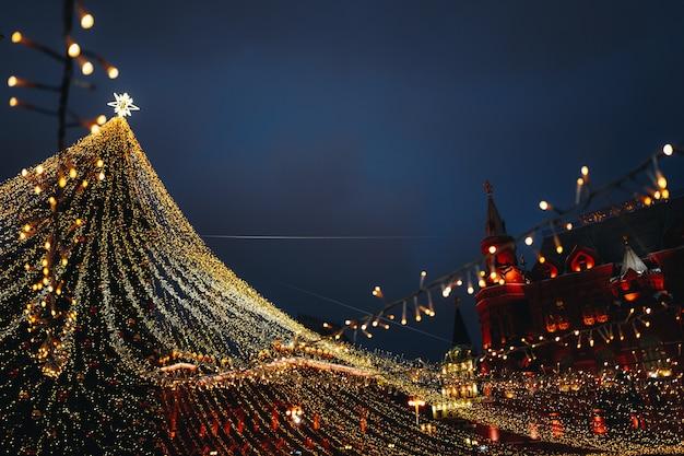 Праздничные сверкающие гирлянды и золотые украшения с елкой как символ нового года