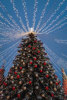 新年あけましておめでとうございますのシンボルとしてクリスマスツリーとお祝いのきらめく花輪と光沢のある装飾