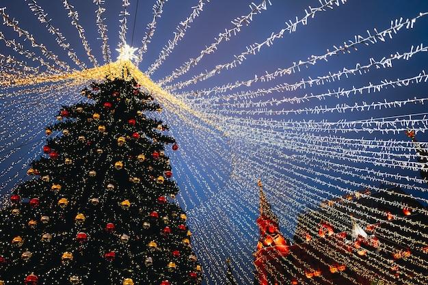 Праздничные сверкающие золотые гирлянды и украшения с елкой как символ нового года