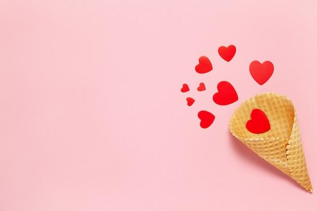 Праздничная весенняя плоская планировка. красные сердца в вафельном рожке на пастельно-розовом фоне. концепция валентина