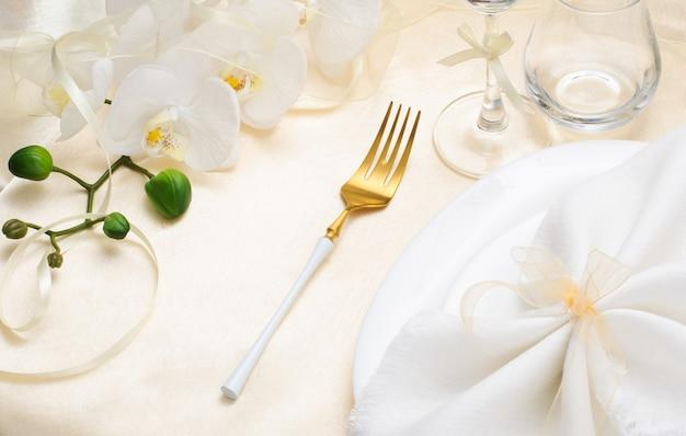 Праздничная весенняя сервировка стола с белой салфеткой и белыми орхидеями на бежевой шелковой скатерти