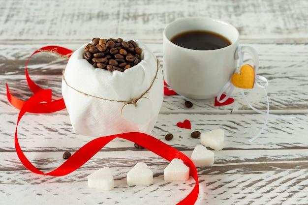 お祝いの聖バレンタインの構成。ハートサシェイプの砂糖と赤い散らばった紙のハートの紙吹雪が入った黒いロマティックコーヒー。