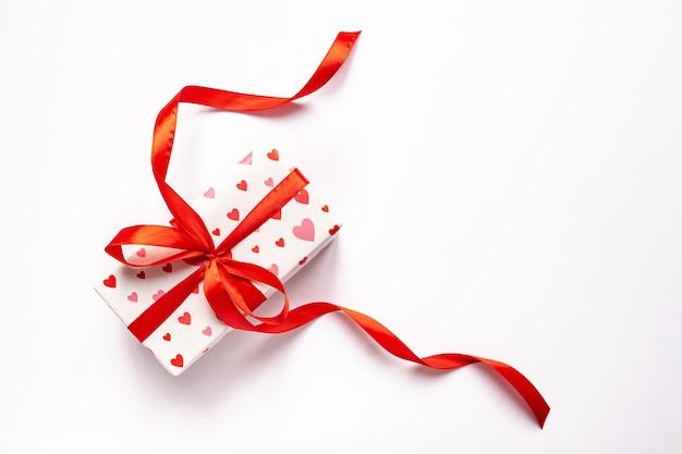 Праздничная концепция дня святого валентина с подарочной коробкой на белой поверхности. вид сверху, копия пространства.