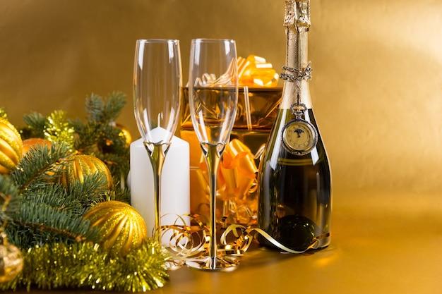 お祝いの静物-クリスマスプレゼントと金のクリスマスボールと見掛け倒しで飾られたエバーグリーンと金色の背景にグラスのペアでシャンパンのボトルに覆われたアンティーク懐中時計