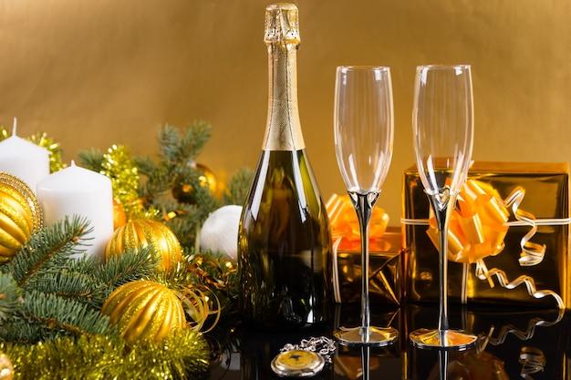 お祝いの静物-クリスマスボールと見掛け倒しで飾られたギフト、キャンドル、常緑樹の黄金の背景の前にシャンパンとグラスのボトルが付いたアンティーク懐中時計