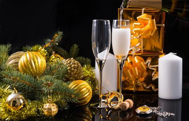 お祝いの静物-懐中時計、白いキャンドル、ゴールドギフト、クリスマスボールと見掛け倒しで飾られた常緑樹と黒の背景にエレガントなシャンパングラスのクローズアップ