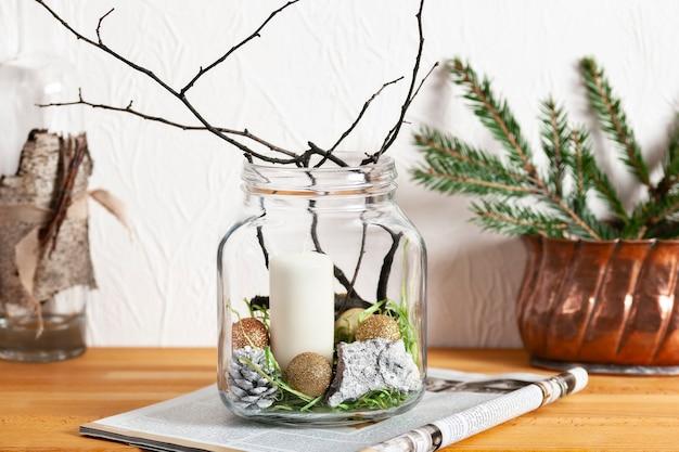 Праздничный натюрморт, современный домашний декор. свеча, шишка, кора и сухая ветка дерева в стеклянной банке стоит в журнале.