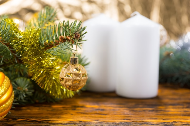 Festive still life of evergreen branches decorated with gold balls and tinsel garland on rustic wooden table with two white unlit pillar candles with copy space in foreground