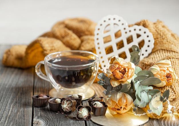 Праздничный натюрморт на день святого валентина с напитком в чашке, шоколадом и цветами на размытом фоне.