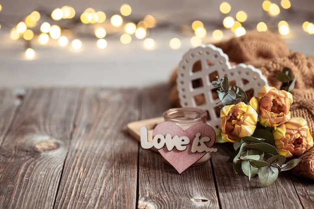 Festive still life love it with flowers and decor details on a wooden surface against a blurred background with bokeh.