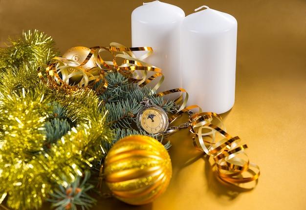 ゴールドのリボン、白い柱のキャンドル、ゴールドの見掛け倒しのガーランドとクリスマスボールで飾られた常緑の枝を備えたアンティーク懐中時計のお祝いの静物 Premium写真