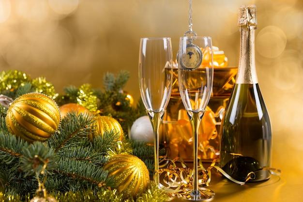 ゴールドのラップされたギフトとゴールドのクリスマスボールと見掛け倒しのガーランドで飾られた常緑の枝と黄色の背景にエレガントなグラスとシャンパンボトルのお祝いの静物