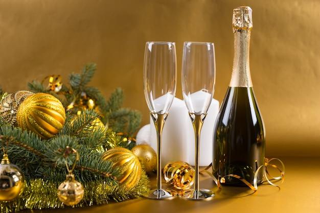 白い柱のキャンドルとゴールドのクリスマスボールと見掛け倒しで飾られた常緑樹の枝と金色の背景にエレガントなグラスとシャンパンのボトルのお祝いの静物