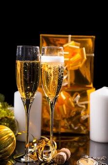 お祝いの静物-金で包まれたギフト、白いキャンドル、クリスマスの装飾と黒の背景の前にスパークリングシャンパンで満たされたグラスのペア
