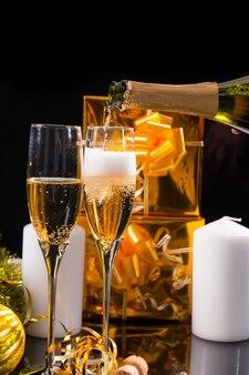 お祝いの静物-白いキャンドルとゴールドラップギフトで黒い背景の前にグラスにシャンパンを注ぐ